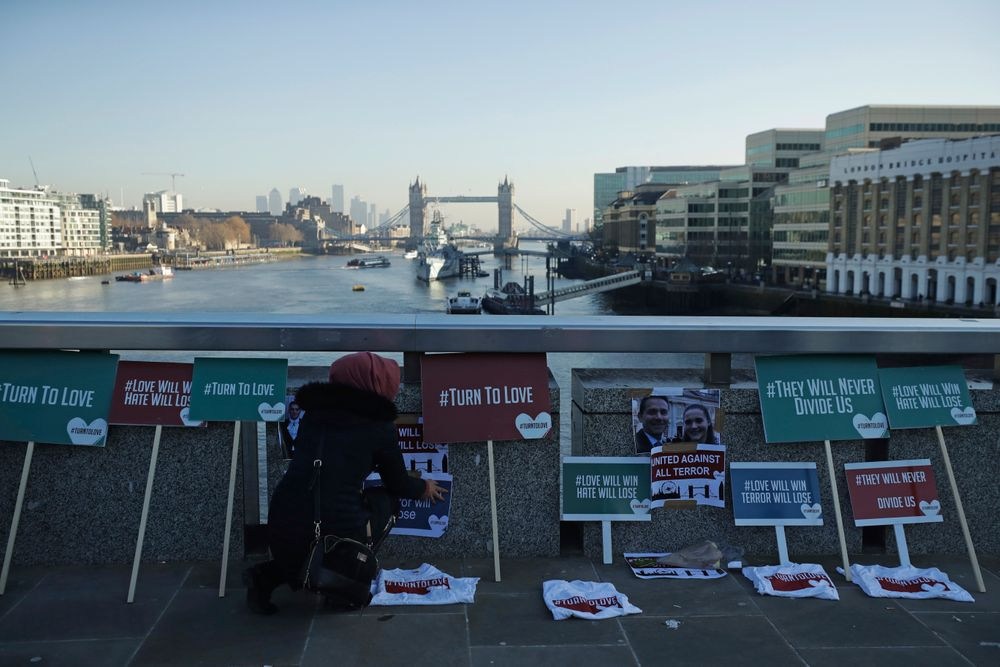 A member of the Faiths Forum for London places tributes on London Bridge in London, Monday, Dec. 2, 2019. London Bridge reopened to cars and pedestrians Monday, three days after a man previously convicted of terrorism offenses stabbed two people to death and injured three others before being shot dead by police. (AP Photo/Matt Dunham)
