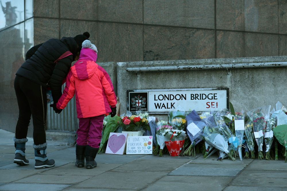 Passers-by stop to look at flowers left at London Bridge following the attack on Friday, in London, Monday, Dec. 2, 2019. London Bridge reopened to cars and pedestrians Monday, three days after a man previously convicted of terrorism offenses stabbed two people to death and injured three others before being shot dead by police. (Yui Mok/PA via AP)