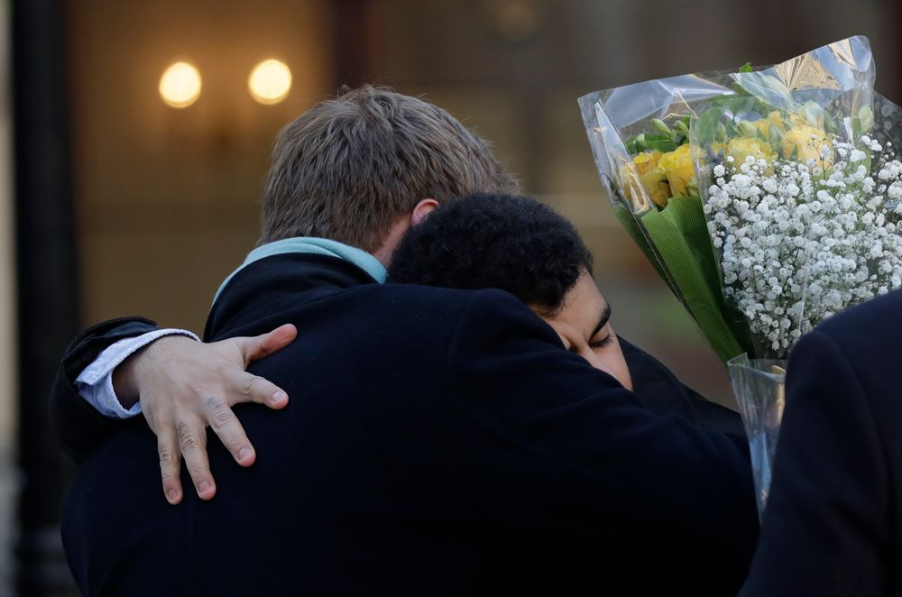 People embrace before attending a vigil at Guildhall Yard in London, Monday Dec. 2, 2019, to remember the London attack victims and honor members of the emergency services and bystanders who fought the attacker. London Bridge reopened to cars and pedestrians Monday, three days after a man previously convicted of terrorism offenses stabbed two people to death and injured three others before being shot dead by police. (AP Photo/Matt Dunham)