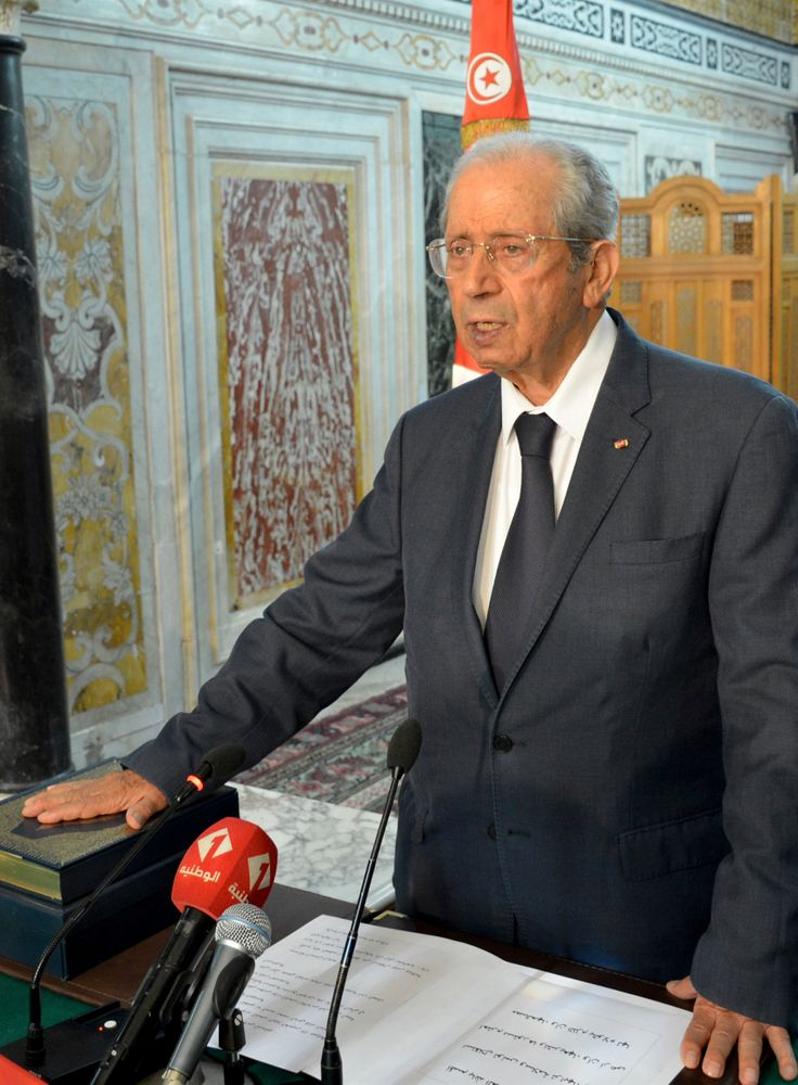 Tunisian parliament president Mohamed Ennaceur, puts his hand on the Quran to be sworn in as Tunisian interim President in Tunis, Tunisia, Thursday, July 25, 2019. Ennaceur, the leader of Tunisia's parliament has been sworn in as the interim president of the North African country after 92-year-old President Beji Essebsi died in office. The state news agency TAP reported that Mohamed Ennaceur, president of the Assembly of People's Representatives, took the oath of office Thursday July 25, hours after Essebsi's death in the morning. (Lassad Manai/Tunisian Assembly via AP)