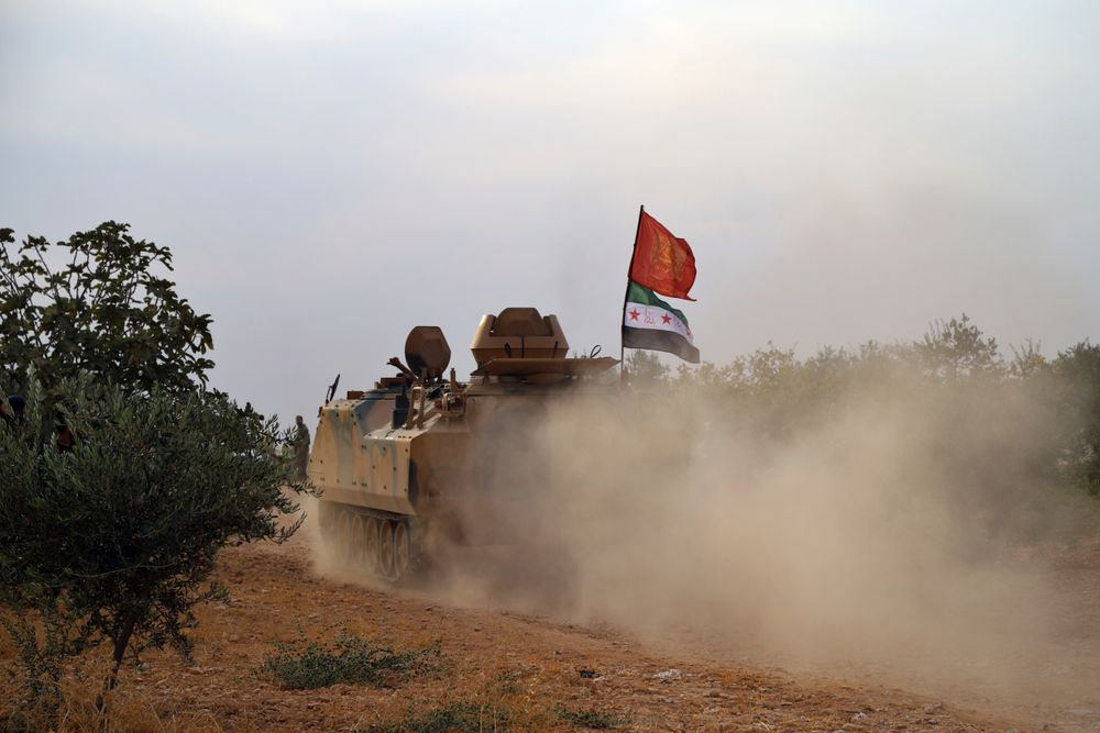In this Monday, Oct. 14, 2019 photo, Turkey-backed Syrian opposition fighters move in an armored vehicle in Syria's northern region of Manbij. Syrian state media said Tuesday that government forces have entered the center of the once Kurdish-held northern town of Manbij and raised the national flag. (AP Photo)