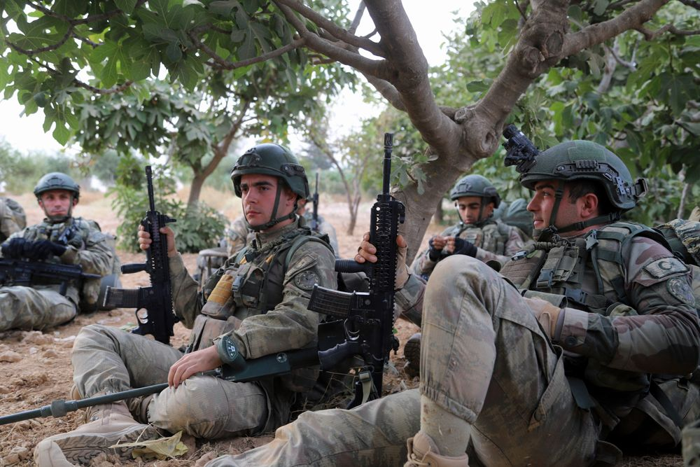 In this Monday, Oct. 14, 2019 photo, Turkish troops rest under trees in Syria's northern region of Manbij. Syrian state media said Tuesday that government forces have entered the center of the once Kurdish-held northern town of Manbij and raised the national flag. (AP Photo)