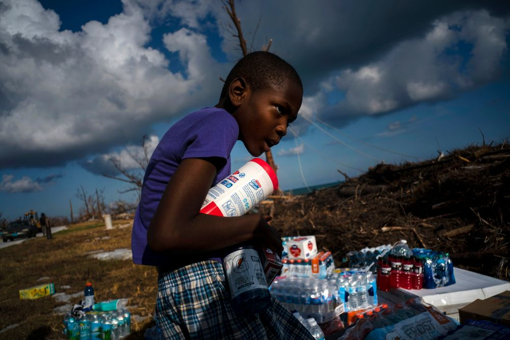 Ayfon Minus, 8, collects donated food that was brought by helicopter from Freeport to the Hurricane Dorian destroyed village of High Rock, Grand Bahama, Bahamas, Tuesday, September 10, 2019. (AP Photo/Ramon Espinosa)