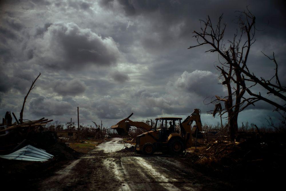 Mos Antenor, 42, drives a bulldozer while clearing the road after Hurricane Dorian Mclean's Town, Grand Bahama, Bahamas, Friday Sept. 13, 2019. (AP Photo/Ramon Espinosa)