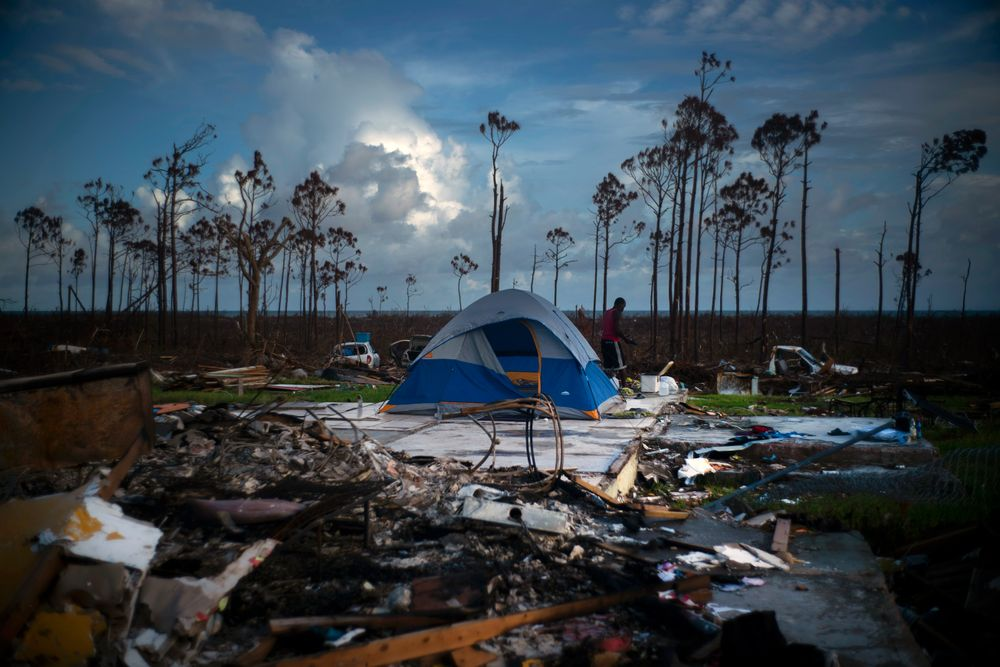 A man searches in the rubble of his house destroyed by Hurricane Dorian in Rocky Creek East, Grand Bahama, Bahamas, Thursday Sept. 12, 2019. Nearly two weeks after Hurricane Dorian hit the northern Bahamas, people continue to scan social media, peer under rubble or follow the smell of death in an attempt to find family and friends. (AP Photo/Ramon Espinosa)