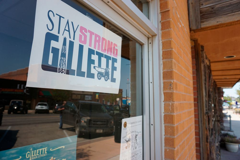 In this Thursday, Sept. 5, 2019 photo shows a poster urging locals to stay strong amid hardship in a Gillette, Wyo, storefront on the Eagle Butte mine just north of Gillette, Wyo. The shutdown of Blackjewel LLC's Belle Ayr and Eagle Butte mines in Wyoming since July 1, 2019 has added yet more uncertainty to the Powder River Basin's struggling coal economy. (AP Photo/Mead Gruver)