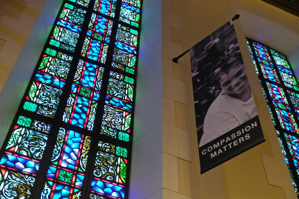 FILE - In this Feb. 12, 2019 file photo, a banner hangs by a stained glass window in the sanctuary at Glide Memorial United Methodist Church in San Francisco. Most Americans don't typically reach out to religious leaders for guidance, according to a poll from The Associated Press-NORC Center for Public Affairs Research. The poll shows the lack of personal connection with ministers even includes people who identify with a religion, though it's less prevalent among those most engaged with their faith. (AP Photo/Eric Risberg)