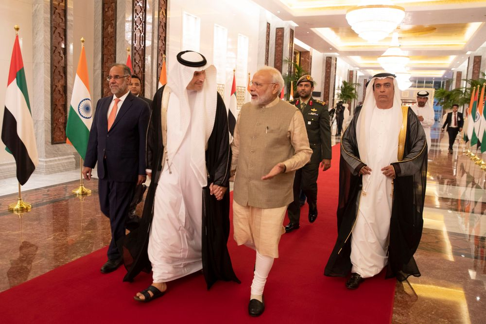 In this photo released by the state-run WAM news agency, Indian Prime Minister Narendra Modi, center right, walks with Khaldoon Khalifa al-Mubarak, chairman of the Abu Dhabi Executive Affairs Authority, center left, after arriving in Abu Dhabi, United Arab Emirates, Friday, Aug. 23, 2019. Modi is on a trip to both the United Arab Emirates and Bahrain, reinforcing ties between India and the Gulf Arab nations as he pursues stripping statehood from the disputed Muslim-majority region of Kashmir. (WAM via AP)
