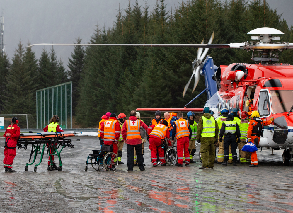 Passengers are helped from a rescue helicopter in Fraena, Norway, Sunday March 24, 2019, after being rescued from the Viking Sky cruise ship. Rescue workers are evacuating more passengers from a cruise ship that had engine problems in bad weather off Norway's western coast while authorities prepare to tow the vessel to a nearby port. (Svein Ove Ekornesvag/NTB Scanpix via AP)