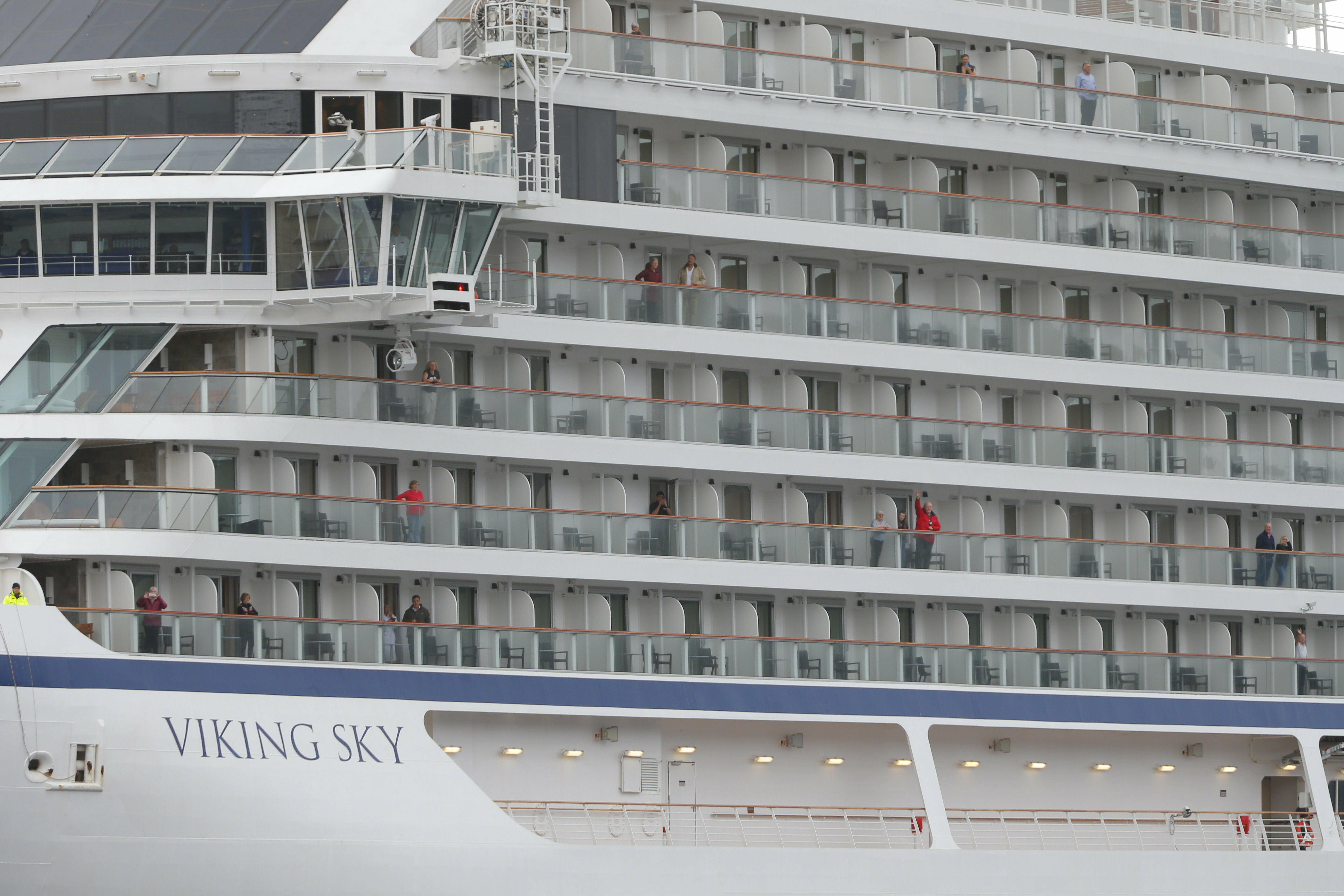 Some of the remaining passengers look out as the cruise ship Viking Sky arrives at port off Molde, Norway, Sunday March 24, 2019, after having problems and issuing a Mayday call on Saturday in heavy seas off Norway's western coast. Rescue helicopters took more than 475 passengers from a cruise ship that got stranded off Norway's western coast in bad weather before the vessel departed for a nearby port under escort and with nearly 900 people still on board, the ship's owner said Sunday. (Svein Ove Ekornesvag/NTB scanpix via AP)