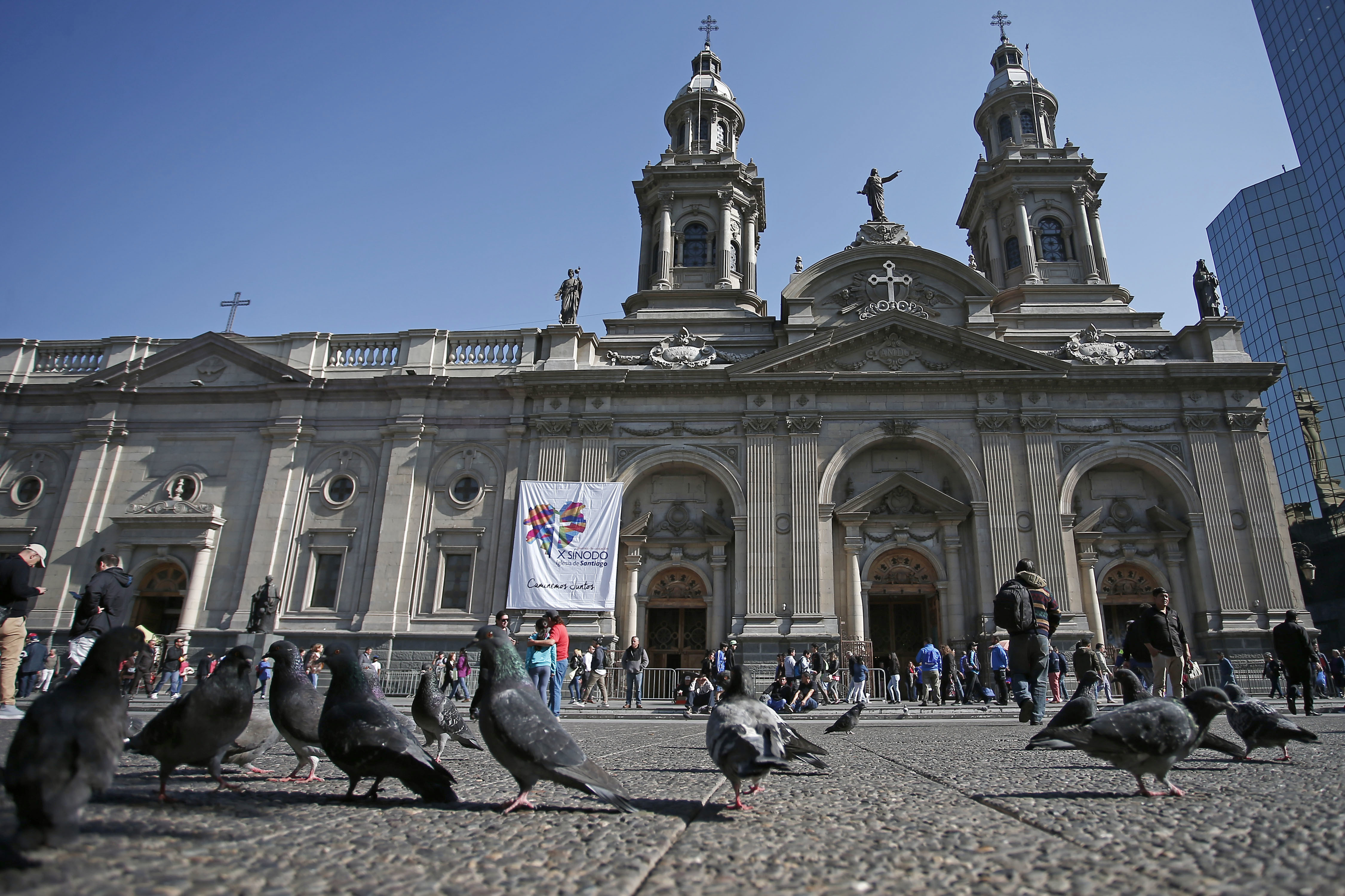 FILE - In this May 18, 2018 file photo, pigeons are fed in front of the Santiago Cathedral, in Santiago, Chile. Pope Francis' high-stakes sex abuse prevention summit is meant to call attention to the crisis as a global problem that requires a global response. Francis discovered first-hand just how pervasive clerical sex abuse is — and how effectively it has been covered up by the Catholic hierarchy — when in January 2018 he branded as