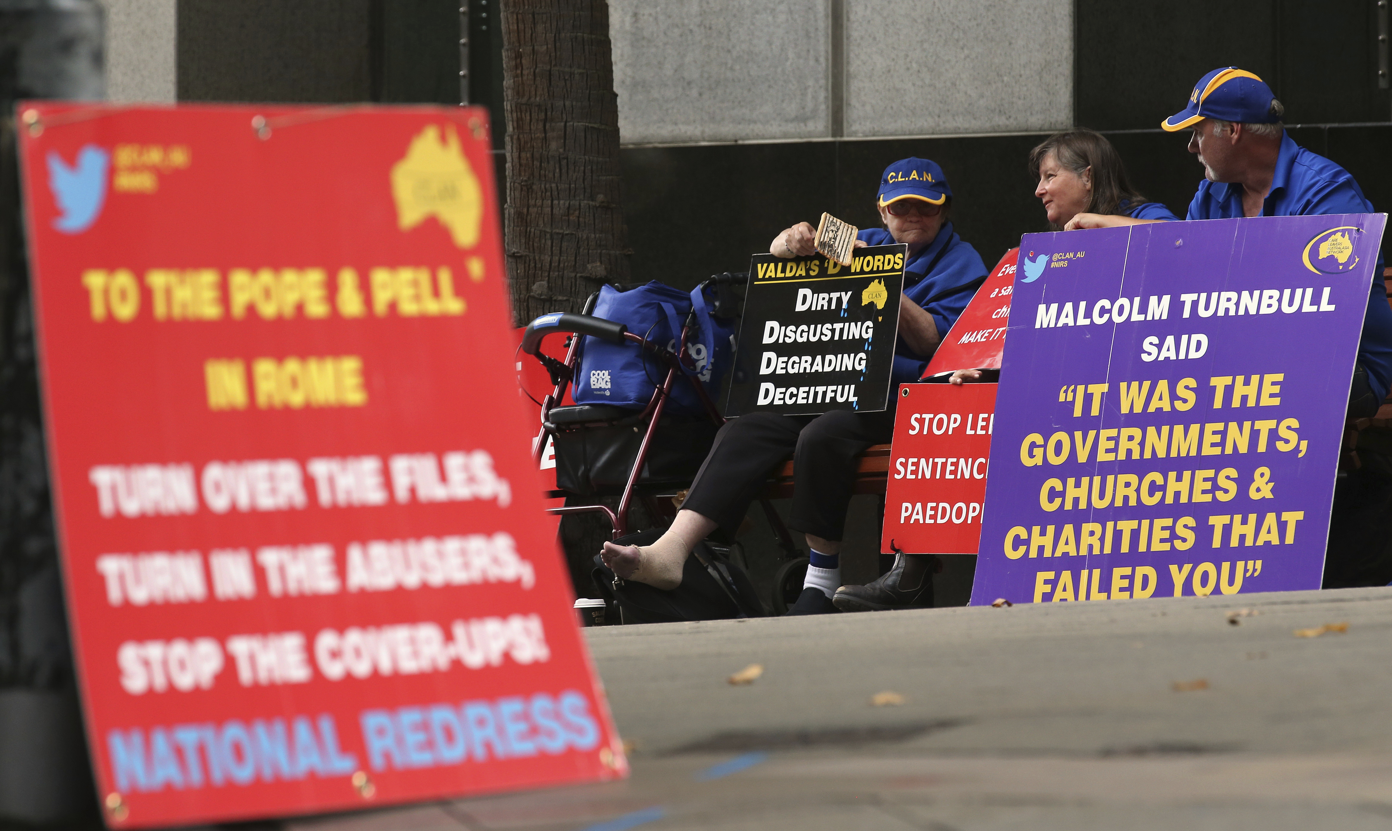 FILE - In this March 1, 2016 file photo, a group gathers to protest with placards outside an inquiry into child sex abuse in Sydney. Pope Francis' high-stakes sex abuse prevention summit is meant to call attention to the crisis as a global problem that requires a global response. Australia's Catholic Church has a horrific abuse record, which in part prompted the government to launch a four-year national investigation into all forms of institutional abuse — Catholic and otherwise.  (AP Photo/Rick Rycroft, file)