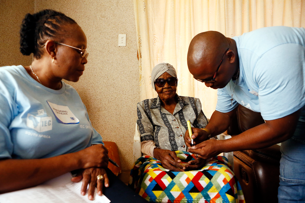 Electoral officials help 108-year-old MMaphuti Mabitsela cast her special vote, at her home in Atteridgeville, near Pretoria, South Africa on Monday May 6, 2019. Mabitsela took part in South Africa's special voting for the elderly and infirm where electoral officials go to their homes or care facilities before the actual voting day of May 8. (AP Photo/Phill Magakoe)