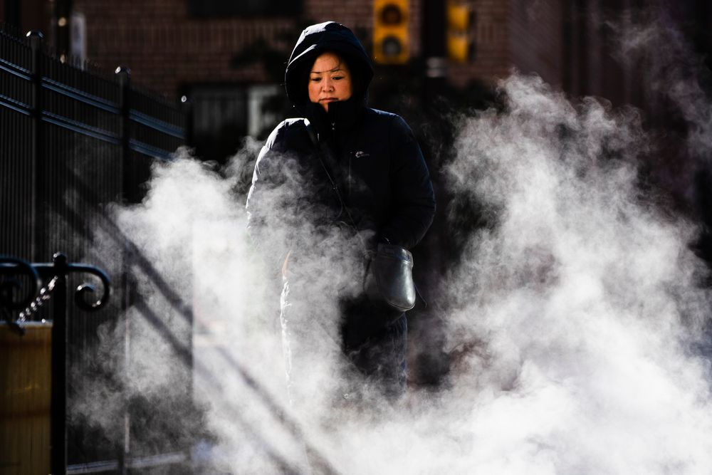 A woman bundled up against the cold walks on an autumn morning in Philadelphia, Wednesday, Nov. 13, 2019.  An arctic blast that sent shivers across the Midwest spread to the eastern U.S. on Wednesday, with bitter weather establishing new records from Mississippi to Maine. (AP Photo/Matt Rourke)