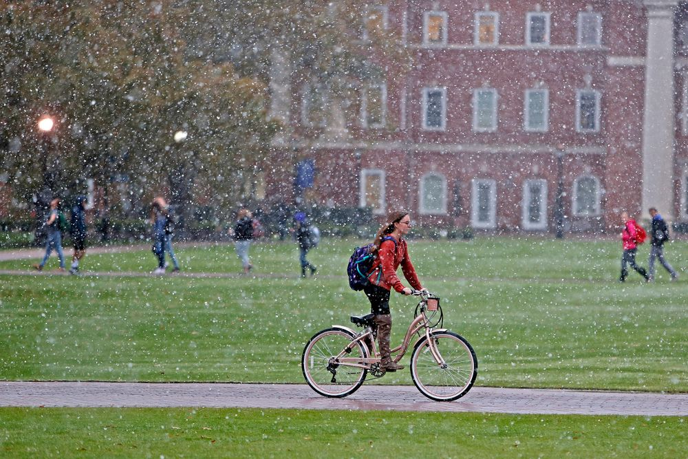 Christopher Newport University students make their way through campus as snow falls, Tuesday afternoon, Nov. 12, 2019 in Newport News, Va. (Jonathon Gruenke/The Virginian-Pilot via AP)