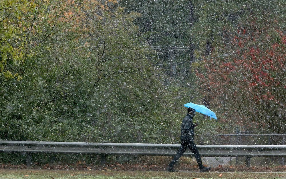 A pedestrian braves the weather as a light snow falls, Tuesday, Nov. 12, 2019 in Newport News, Va. (Rob Ostermaier/The Virginian-Pilot via AP)