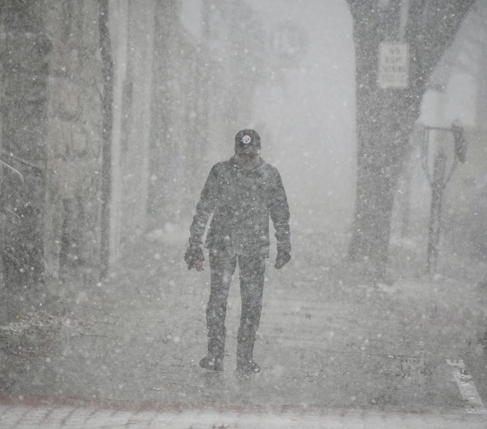 A pedestrian walks through a snow squall in downtown Johnstown, Pa. on Tuesday, Nov. 12, 2019. Snow and icy conditions are slowing traffic in parts of Pennsylvania as  road crews treat surfaces because bitter cold is expected.  (Todd Berkey/The Tribune-Democrat via AP)