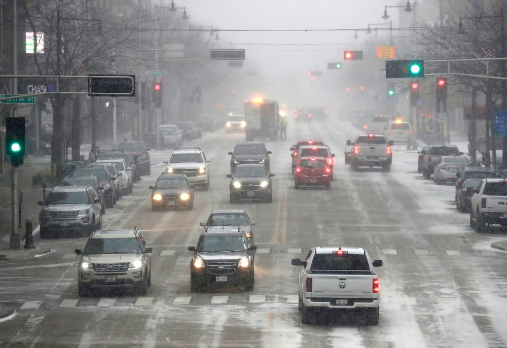 Traffic moves slowly along College Avenue as snow falls Wednesday, Nov. 13, 2019, in Appleton, Wis. (Dan Powers/The Post-Crescent via AP)