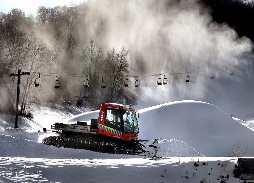 Snow billows from a snowmaker, Tuesday, Nov. 12, 2019, creating piles as Tom Roesler, mountain manager at Mount La Crosse in La Crosse, Wis., spreads it out. Pending weather conditions, Mount La Crosse staff are hoping to open the ski area before the end of the month. (Peter Thomson/La Crosse Tribune via AP)