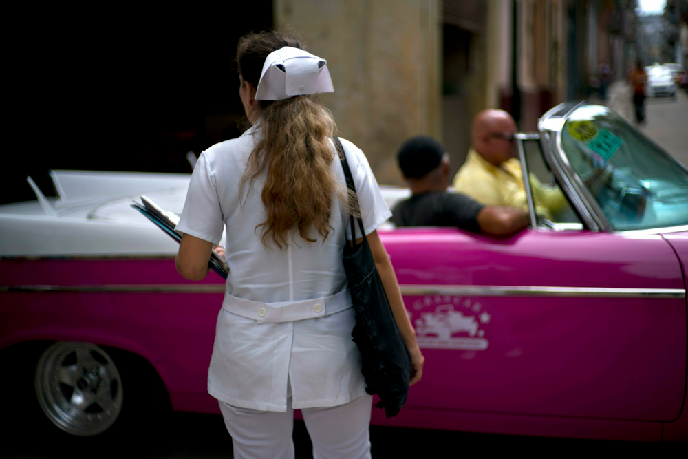 A nurse walks down the street where a classic American car carries tourists in Havana, Cuba, Wednesday, April 10, 2019. Communist Party leader Raúl Castro warned Cubans on Wednesday that they should brace for worsening shortages due to Trump administration policies, but said the island won't return to the extreme deprivation of the post-Soviet period. (AP Photo/Ramon Espinosa)