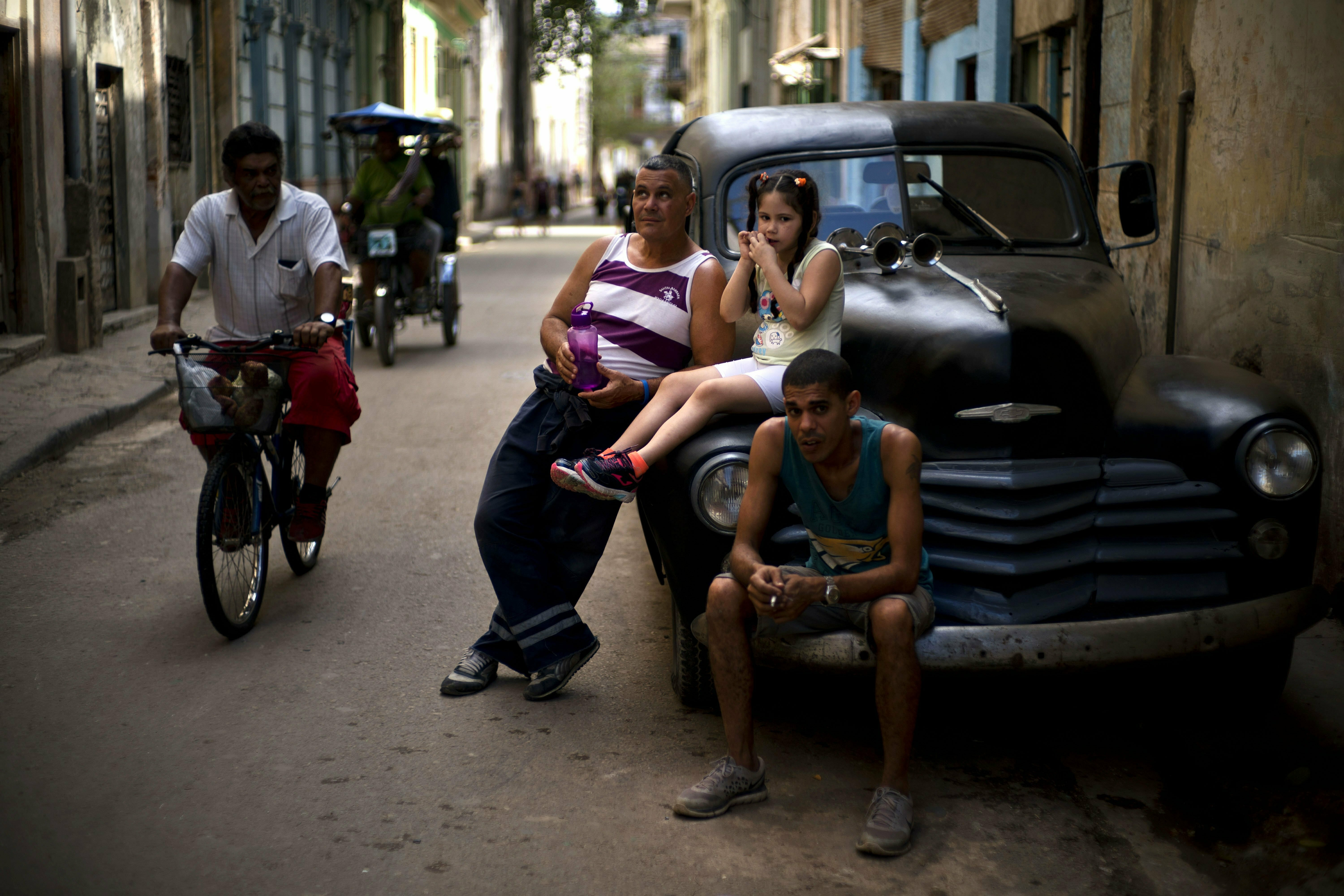 People rest on a classic American car as a man pedals his bike past in Havana, Cuba, Wednesday, April 10, 2019. Communist Party leader Raúl Castro warned Cubans on Wednesday that they should brace for worsening shortages due to Trump administration policies, but said the island won't return to the extreme deprivation of the post-Soviet period. (AP Photo/Ramon Espinosa)