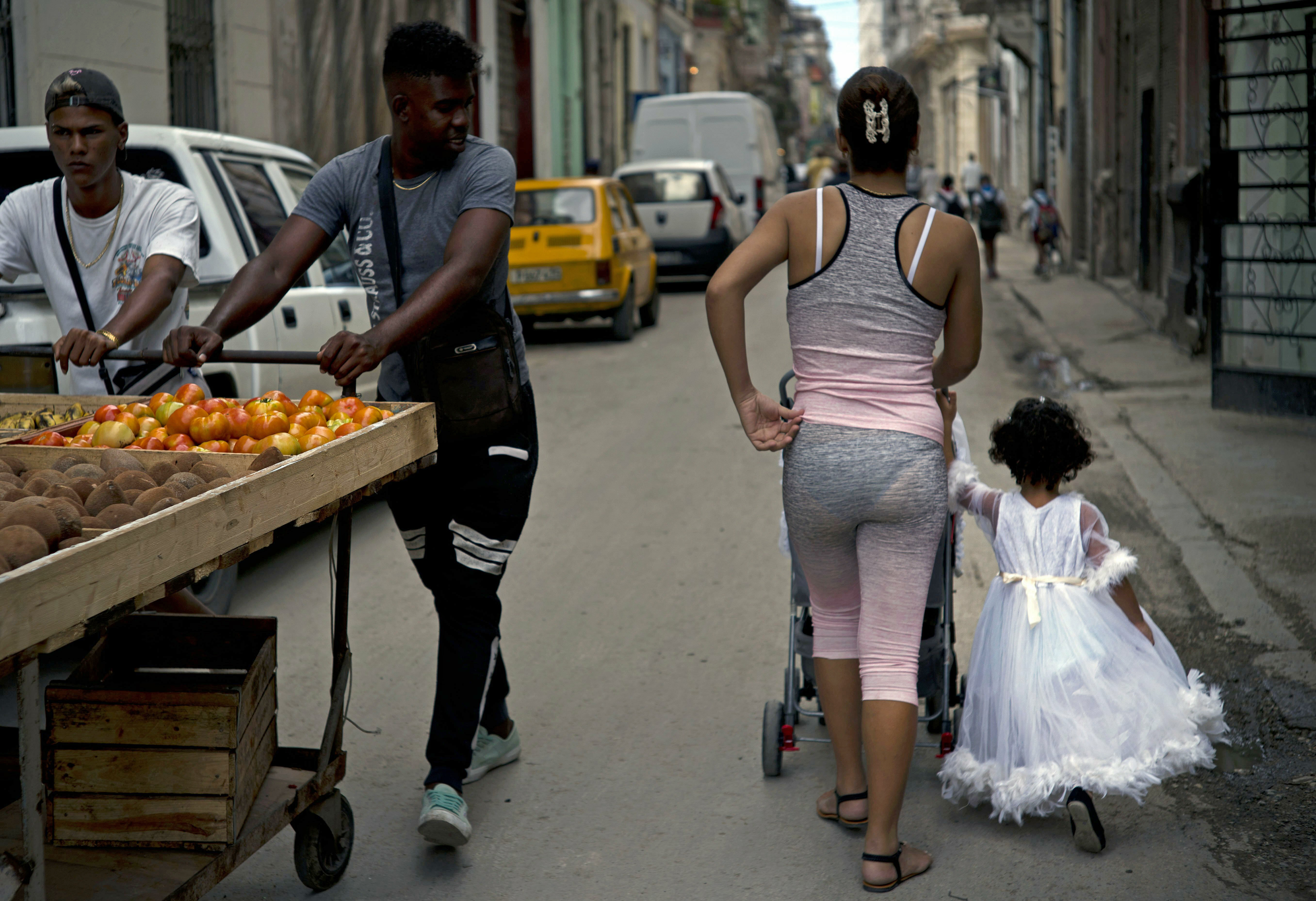 A girl in an angel costume walks with her family past vegetable vendors in Havana, Cuba, Wednesday, April 10, 2019. Communist Party leader Raúl Castro warned Cubans on Wednesday that they should brace for worsening shortages due to Trump administration policies, but said the island won't return to the extreme deprivation of the post-Soviet period. (AP Photo/Ramon Espinosa)