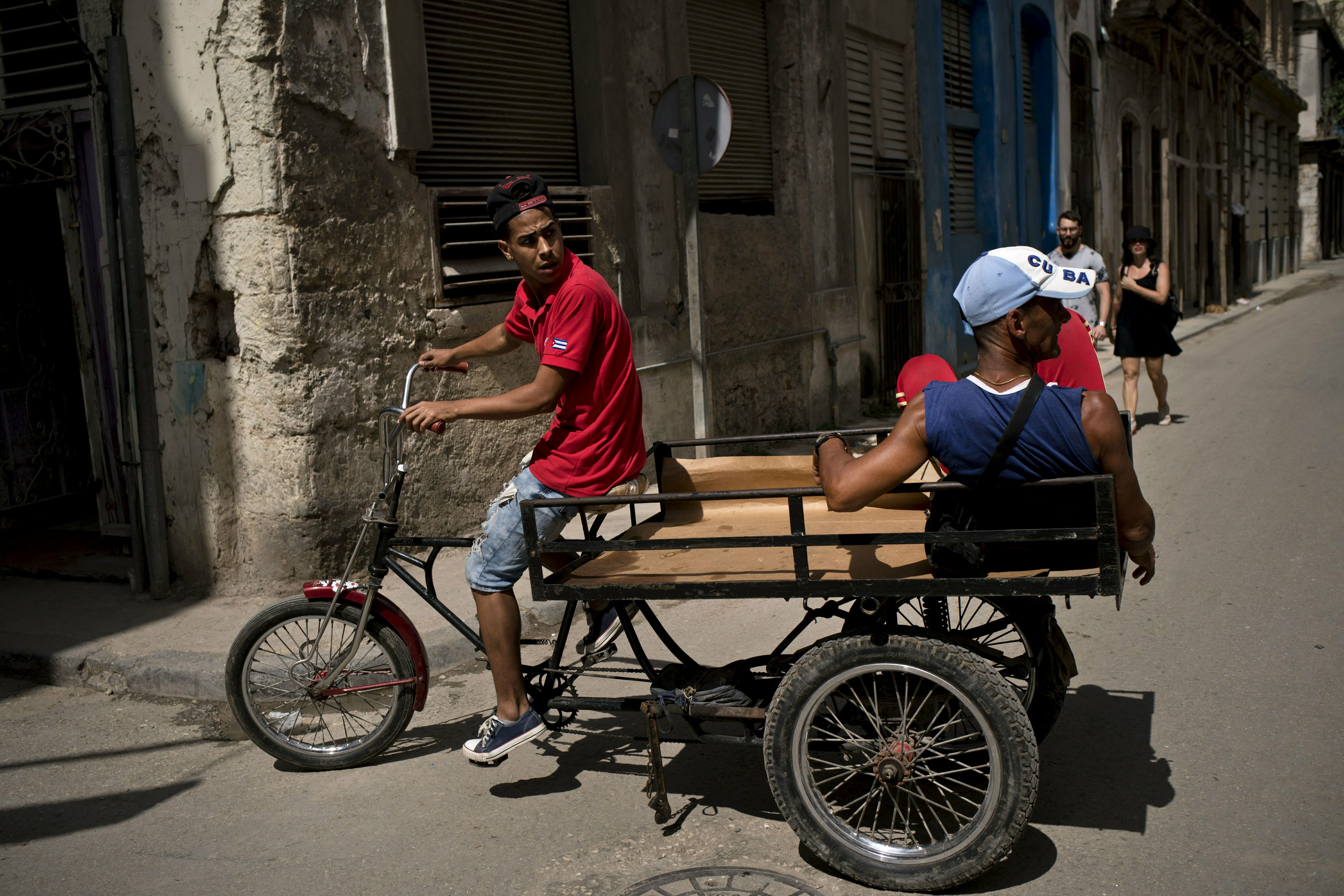 A man pedaling a tricycle equipped with a platform earns a living by transporting passengers through Havana, Cuba, Wednesday, April 10, 2019. Communist Party leader Raúl Castro warned Cubans on Wednesday that they should brace for worsening shortages due to Trump administration policies, but said the island won't return to the extreme deprivation of the post-Soviet period. (AP Photo/Ramon Espinosa)