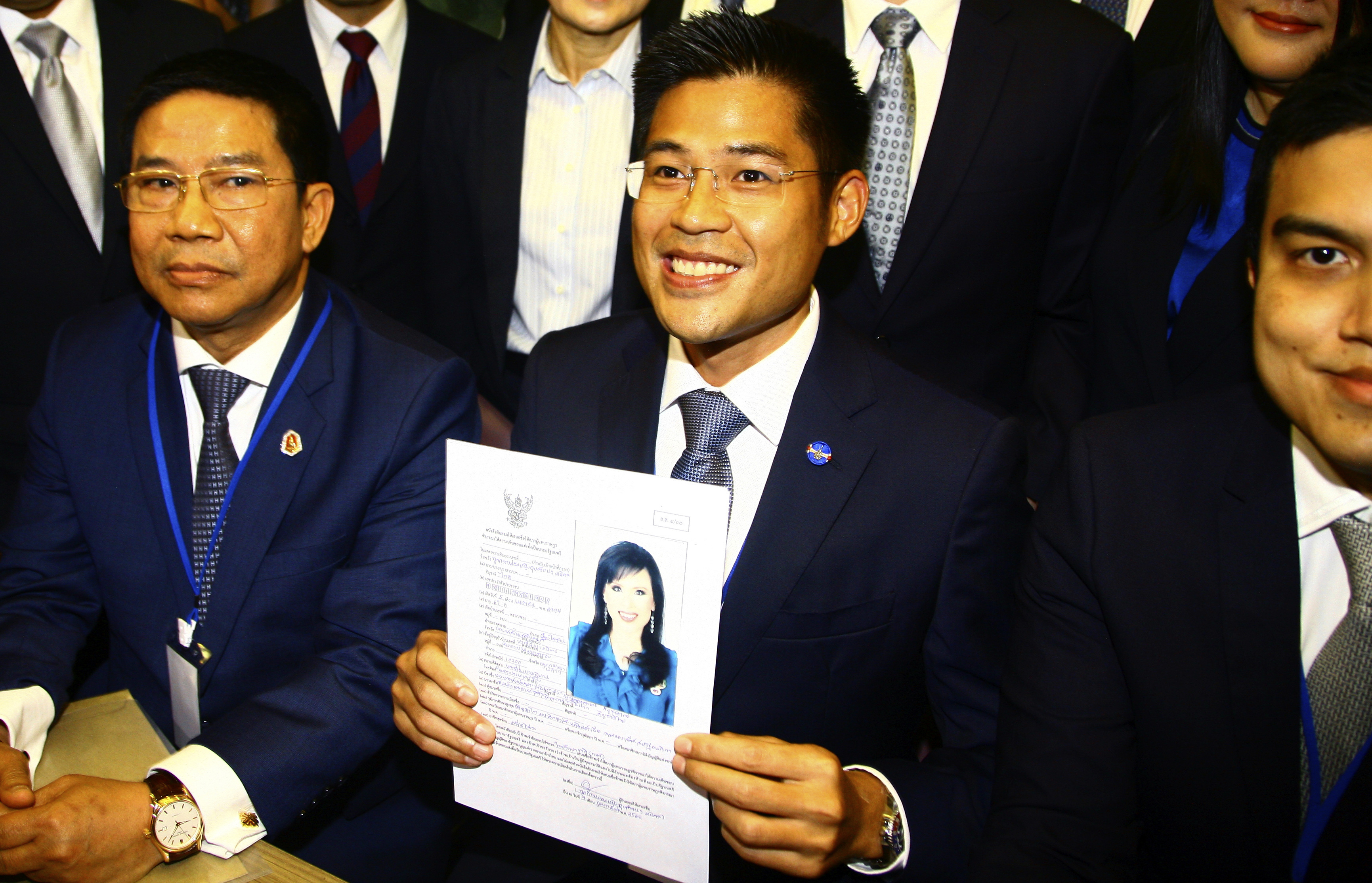Leader of Thai Raksa Chart party Preecha Pholphongpanich, center, holds a picture of Princess Ubolratana at election commission of Thailand in Bangkok, Thailand, Friday, Feb. 8, 2019. The political party has selected the princess as its nominee to serve as the next prime minister, upending tradition that the royal palace plays no public role in politics and upsetting all predictions about what may happen in the March election. (AP Photo)