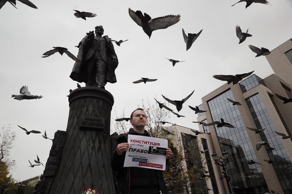 An opposition activist holds a poster reading