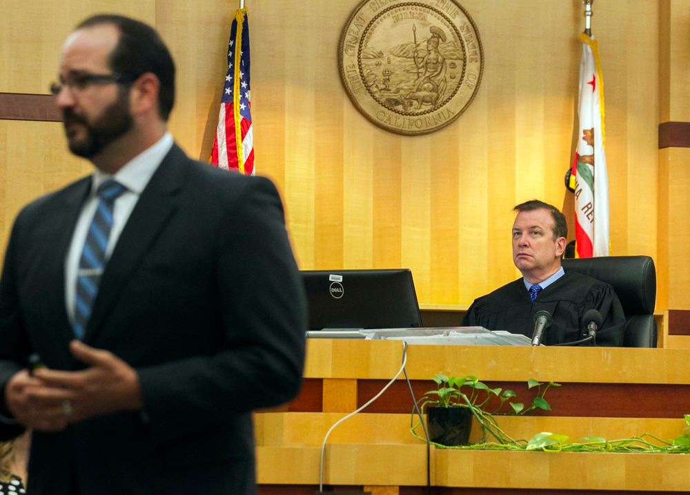 Judge Blaine Bowman, right, listens as Deputy District Attorney Dan Owens gives his opening statement to the jury on the opening day of former NFL football player Kellen Winslow Jr.'s rape trial, Monday, May 20, 2019, in Vista, Calif. (John Gibbins/The San Diego Union-Tribune via AP, Pool)