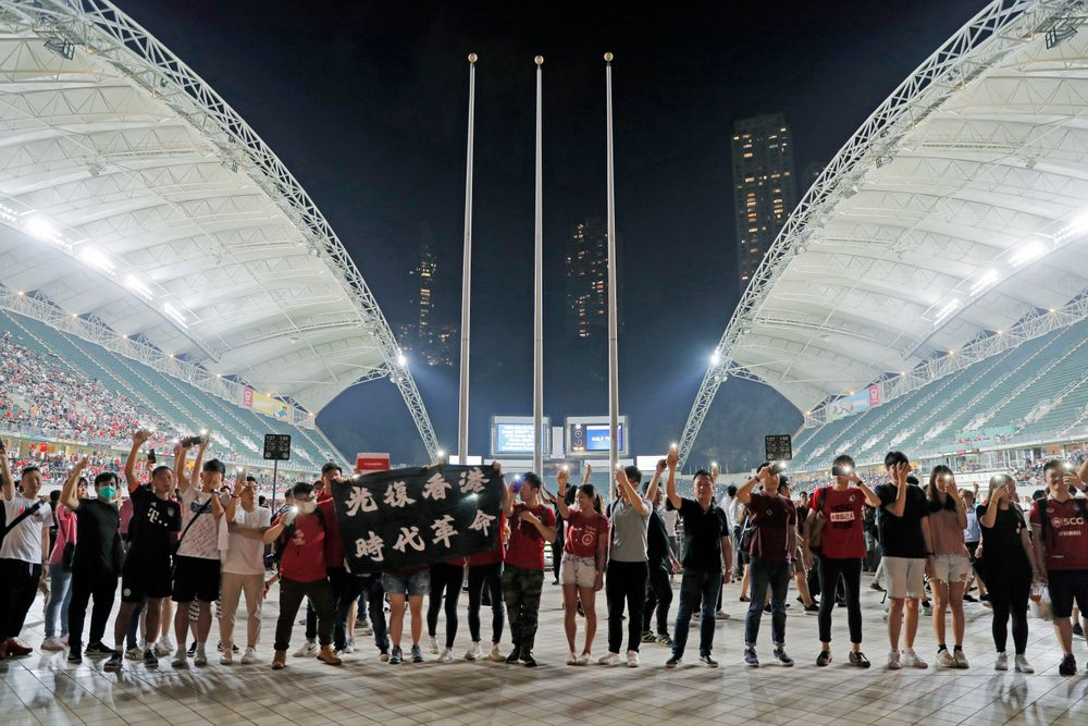 Hong Kong soccer fans form human chain and chant banner reads