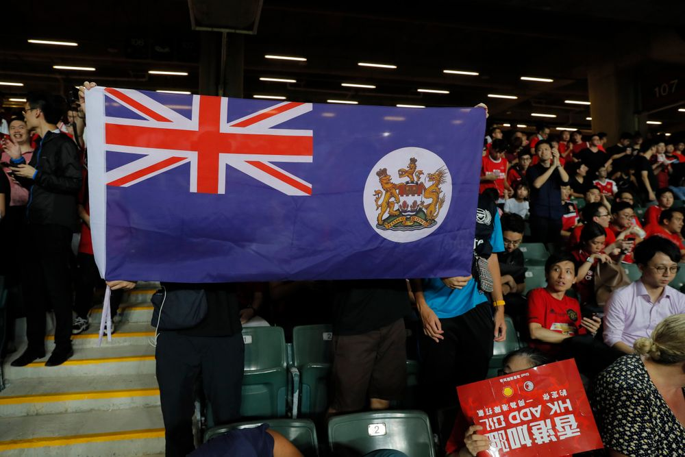 Hong Kong soccer fans hold a colonial era flag of Hong Kong during the FIFA World Cup Qatar 2022 and AFC Asian Cup 2023 Preliminary Joint Qualification Round 2 soccer match between Hong Kong and Iran, in Hong Kong, Tuesday, Sept. 10, 2019. The crowd broke out into
