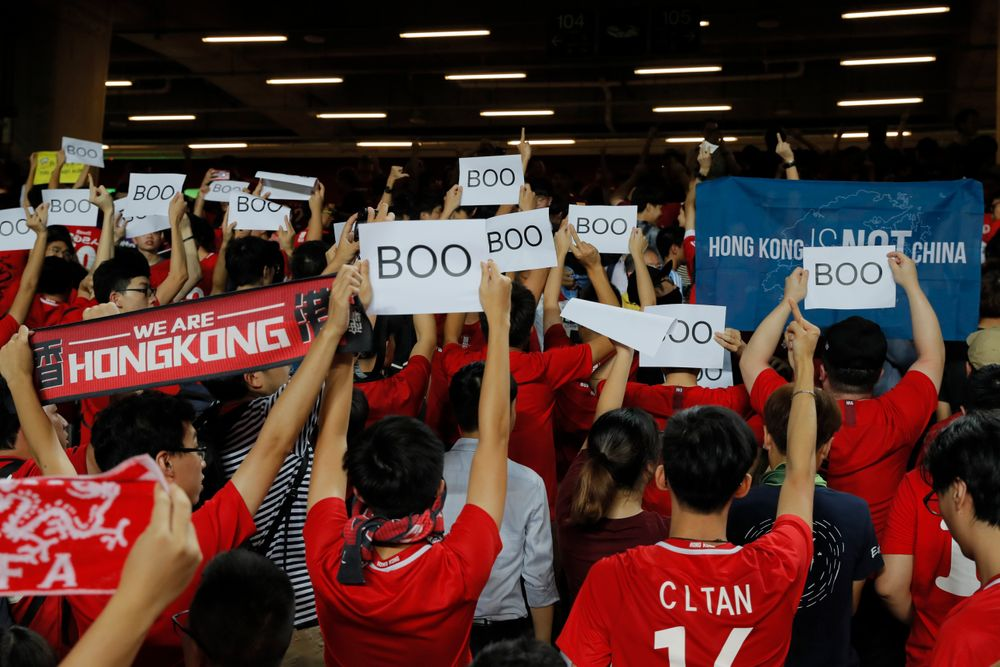 Hong Kong soccer fans turn their back and boo the Chinese national anthem as they chant