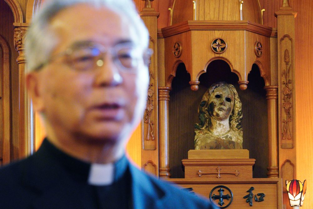 In this Nov. 16, 2019, photo, Japanese Archbishop Mitsuaki Takami, who heads Nagasaki's Catholic community of 60,000, speaks in front of a statue of the Virgin Mary that was damaged in the A-bomb attack at the Urakami Cathedral in Nagasaki, southern Japan. Pope Francis will start his first official visit to Japan in Nagasaki, ground zero for the Christian experience in a nation where the Catholic leader once dreamed of living as a missionary. (AP Photo/Eugene Hoshiko)