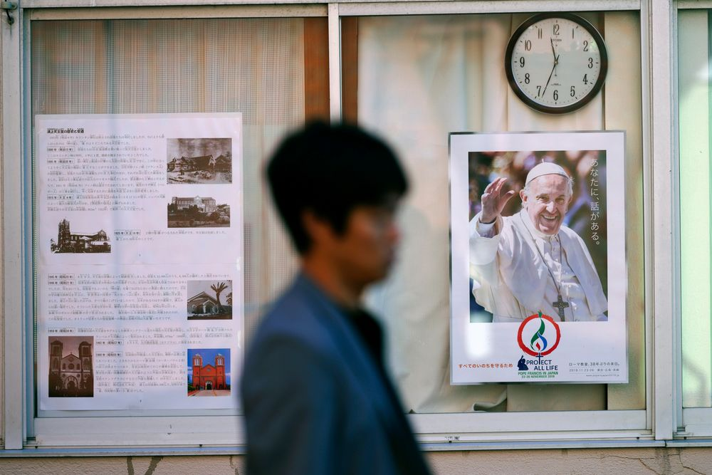 In this Nov. 16, 2019, photo, a man walks by a poster of Pope Francis at the Urakami Cathedral in Nagasaki, southern Japan. Pope Francis will start his first official visit to Japan in Nagasaki, ground zero for the Christian experience in a nation where the Catholic leader once dreamed of living as a missionary. (AP Photo/Eugene Hoshiko)