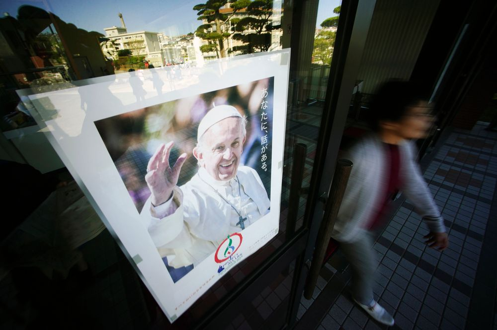 In this Nov. 16, 2019, photo, a woman walks by a poster of Pope Francis at the Urakami Cathedral in Nagasaki, southern Japan. Pope Francis will start his first official visit to Japan in Nagasaki, ground zero for the Christian experience in a nation where the Catholic leader once dreamed of living as a missionary. (AP Photo/Eugene Hoshiko)