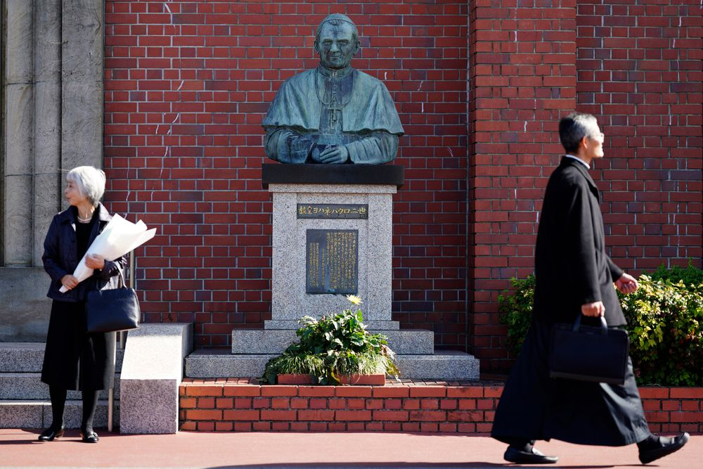 In this Nov. 16, 2019, photo, people walk past a statue of the late Pope John Paul II, who visited Nagasaki in 1981, at the Urakami Cathedral in Nagasaki, southern Japan. Pope Francis will start his first official visit to Japan in Nagasaki, ground zero for the Christian experience in a nation where the Catholic leader once dreamed of living as a missionary. (AP Photo/Eugene Hoshiko)