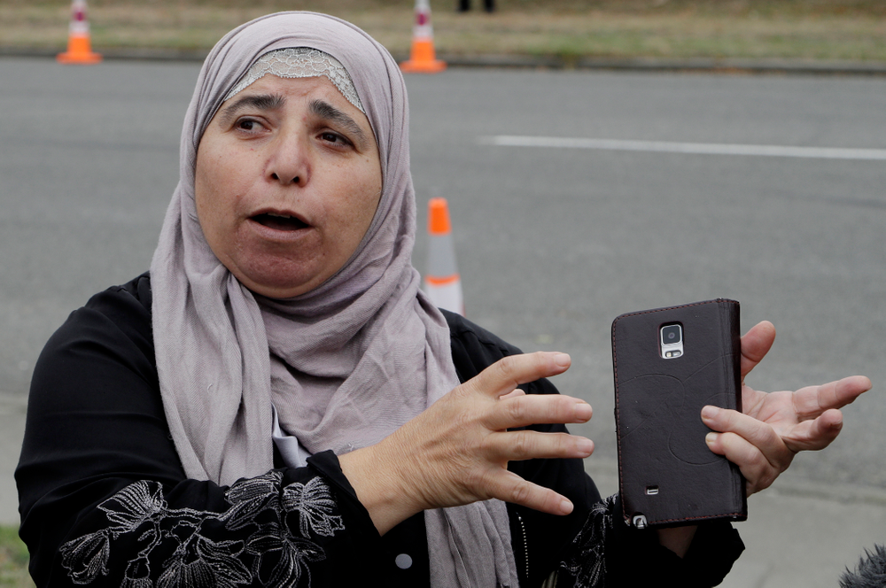 """FILE - In this March 18, 2019, file photo, Al Noor mosque shooting survivor Kawthar Abulaban gestures as she explains escaping from the mosque to media in Christchurch, New Zealand. Abulaban was in the women's prayer area with other women. She heard a single shot at first, enough for some of them to jump up and say, """"What's wrong?"""" Then there was a pause and a second shot and a dawning realization. Soon, there was a barrage of bullets. (AP Photo/Mark Baker, File)"""