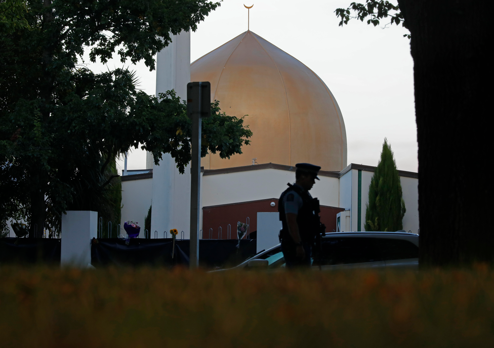 """FILE - In this March 17, 2019, file photo, a police officer stands guard in front of the Al Noor mosque in Christchurch, New Zealand. On Friday, the imam, Gamal Fouda, had just finished the Khutbah, the formal sermon that's delivered in Arabic, and he had started the next part in which he translated it into English. As the gunman approached the mosque, a man in the entrance called out cheerfully, """"Hello, brother."""" Brenton Tarrant fired several shots, one after another, and walked past the first bodies.(AP Photo/Vincent Yu, File)"""