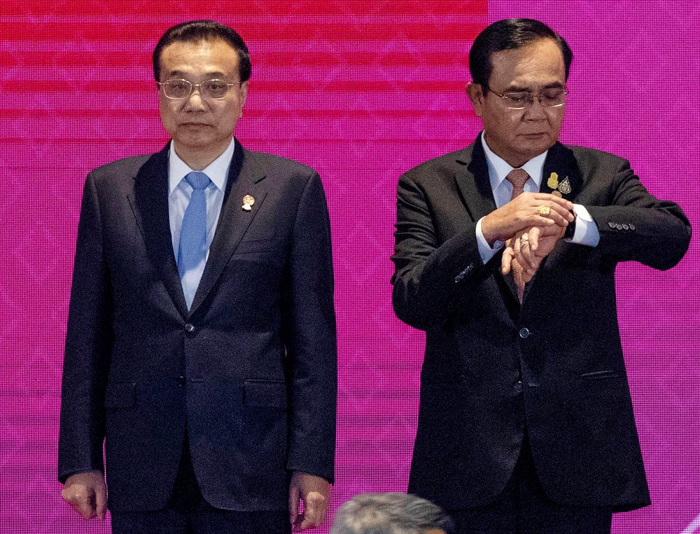 Thailand Prime Minister Prayuth Chan-ocha, right, looks at his watch as Chinese Premier Li Keqiang stands beside him for a group photo at East Asia Summit on the sidelines of the 35th Association of Southeast Asian Nations (ASEAN) summit in Nonthaburi, Thailand, Monday, Nov. 4, 2019. (AP Photo/Wason Wanichakorn)
