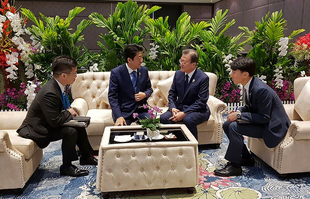 In this photo provided by South Korea Presidential Blue House, South Korean President Moon Jae-in, center right, talks with Japanese Prime Minister Shinzo Abe, center left, ahead of the ASEAN+3 Summit in Nonthaburi, Thailand, Monday, Nov. 4, 2019. (South Korea Presidential Blue House via AP)
