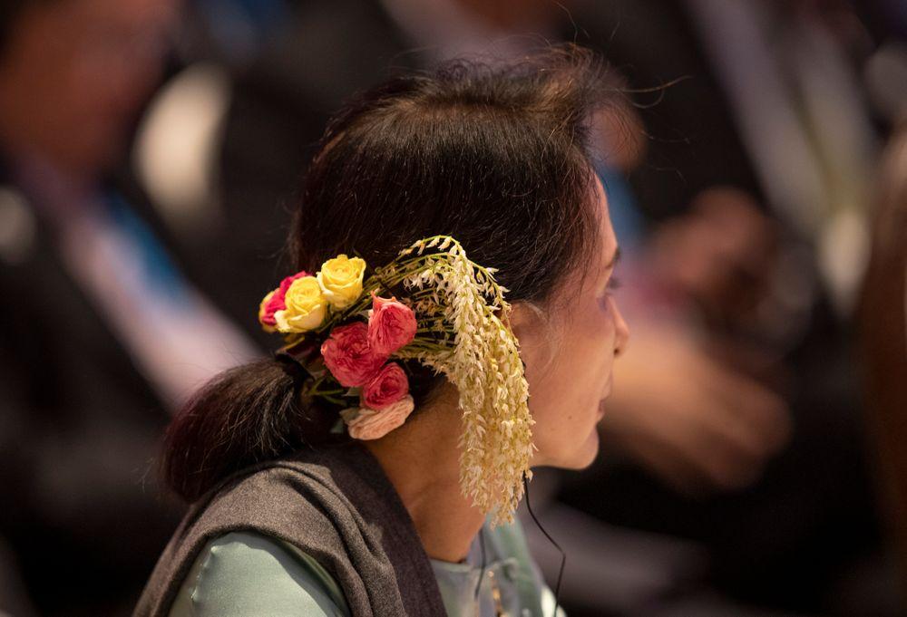 Myanmar leader Aung San Suu Kyi wears a floral arrangement in her hair during the ASEAN-Japan summit in Nonthaburi, Thailand, Monday, Nov. 4, 2019. (AP Photo/Gemunu Amarasinghe)