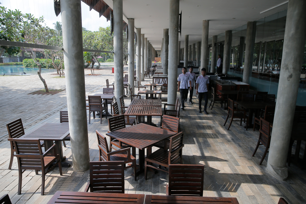 In this Friday, May 10, 2019, photo, hotel staff walk past an empty restaurant at a hotel in Hikkaduwa, Sri Lanka. Sri Lanka was the Lonely Planet guide's top travel destination for 2019, but since the Easter Sunday attacks on churches and luxury hotels, foreign tourists have fled. Hikkaduwa, in the south west, used to be top tourist attraction for the strong waves that were perfect for board-surfing and sparkling clear waters perfect for snorkeling. Today, of the 27 hotels, a very few are still open while most of others along with the eateries lining the six kilometer stretch of palm-fringed beach, are closed. (AP Photo/Eranga Jayawardena)
