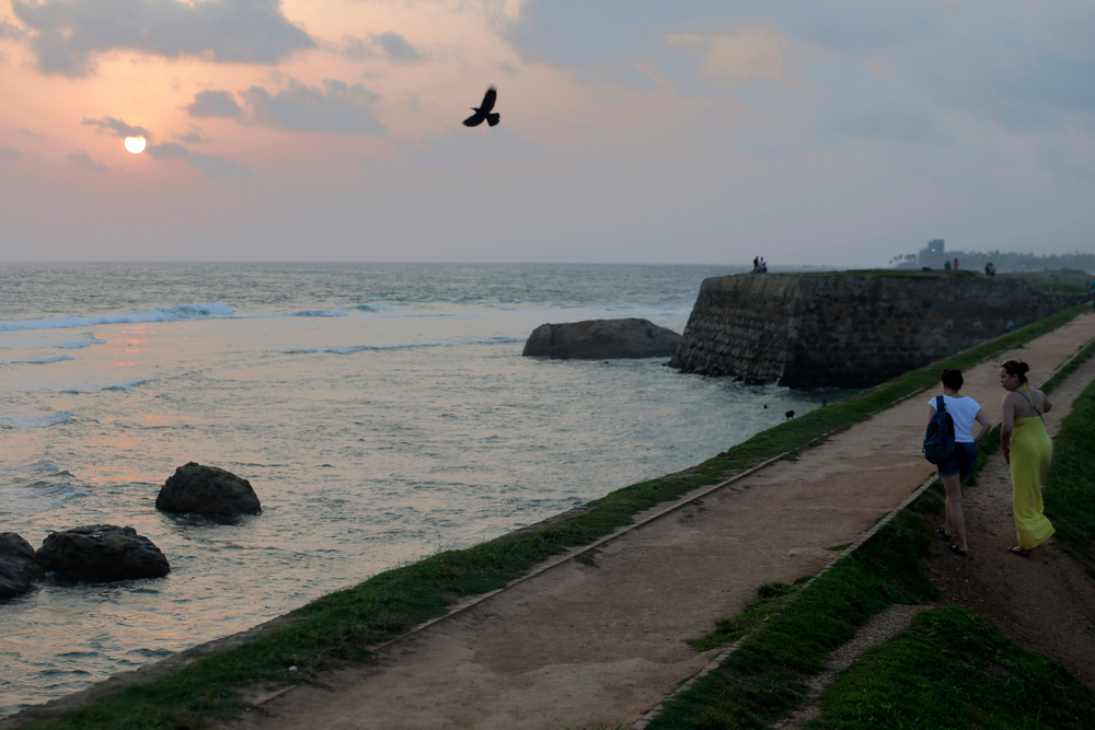In this Friday, May 10, 2019, photo, foreign tourists walk on the rampart of the 17th century built Dutch fort in Galle, Sri Lanka. Sri Lanka was the Lonely Planet guide's top travel destination for 2019, but since the Easter Sunday attacks on churches and luxury hotels, foreign tourists have fled. More than 250 people, including 45 foreigners who are mostly from China, India, the U.S. and the U.K., died in the series of suicide bombings by Islamic State and its local affiliates in churches and hotels in the capital, Colombo, and across the country on April 21. (AP Photo/Eranga Jayawardena)