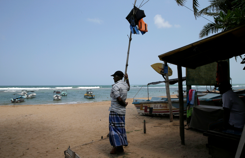 In this Friday, May 10, 2019, photo, a Sri Lankan reef safari boat operator stands on an empty beach in Hikkaduwa, Sri Lanka. Sri Lanka was the Lonely Planet guide's top travel destination for 2019, but since the Easter Sunday attacks on churches and luxury hotels, foreign tourists have fled. Hikkaduwa, in the south west, used to be top tourist attraction for the strong waves that were perfect for board-surfing and sparkling clear waters perfect for snorkeling. Today, of the 27 hotels, a very few are still open while most of others along with the eateries lining the six kilometer stretch of palm-fringed beach, are closed. (AP Photo/Eranga Jayawardena)