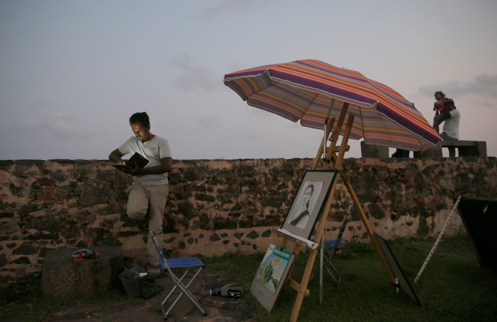 In this Friday, May 10, 2019, photo, a Sri Lankan street painter looks at his mobile phone as locals stand along the 17th century Dutch built rampart of the Galle fort in Galle, Sri Lanka. Sri Lanka was the Lonely Planet guide's top travel destination for 2019, but since the Easter Sunday attacks on churches and luxury hotels, foreign tourists have fled. More than 250 people, including 45 foreigners mainly from China, India, the U.S. and the U.K., died in the Islamic State group-claimed blasts. (AP Photo/Eranga Jayawardena)