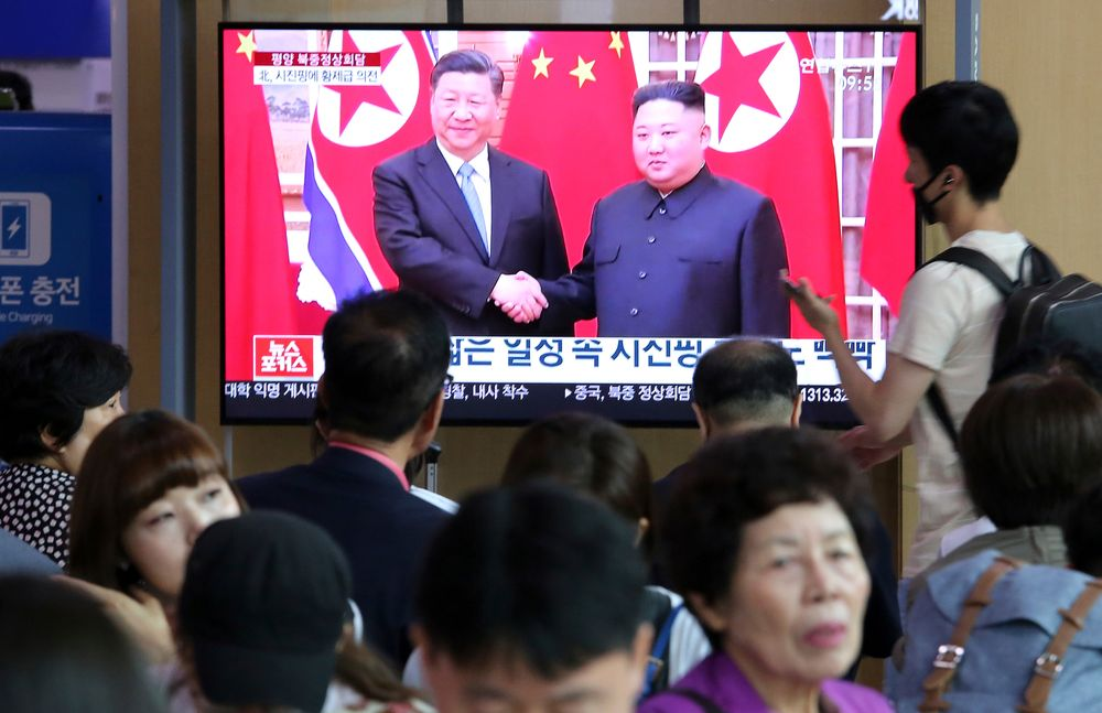 People watch a TV screen showing North Korean leader Kim Jong Un, right, welcoming Chinese President Xi Jinping, at the Seoul Railway Station in Seoul, South Korea, Friday, June 21, 2019. North Korea's state media says leader Kim Jong Un and Chinese President Xi Jinping held broad discussions over the political situation surrounding the Korean Peninsula and called for stronger bilateral ties in the face of