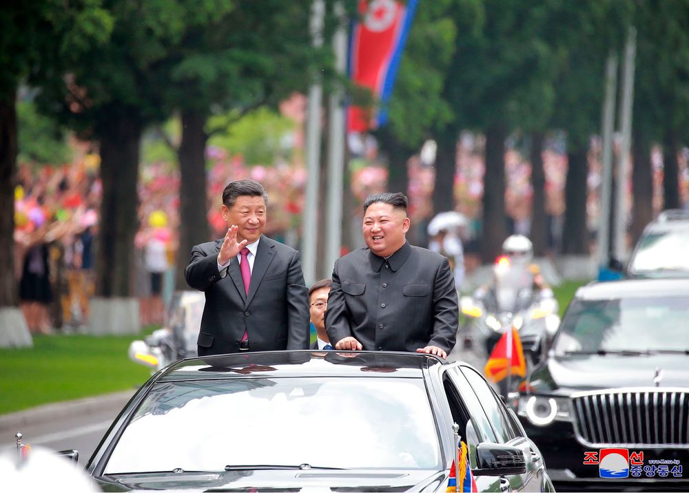 In this Thursday, June 20, 2019, photo provided by the North Korean government, North Korean leader Kim Jong Un, right, and Chinese President Xi Jinping acknowledge welcoming people from the limousine in Pyongyang, North Korea. The content of this image is as provided and cannot be independently verified. Korean language watermark on image as provided by source reads: