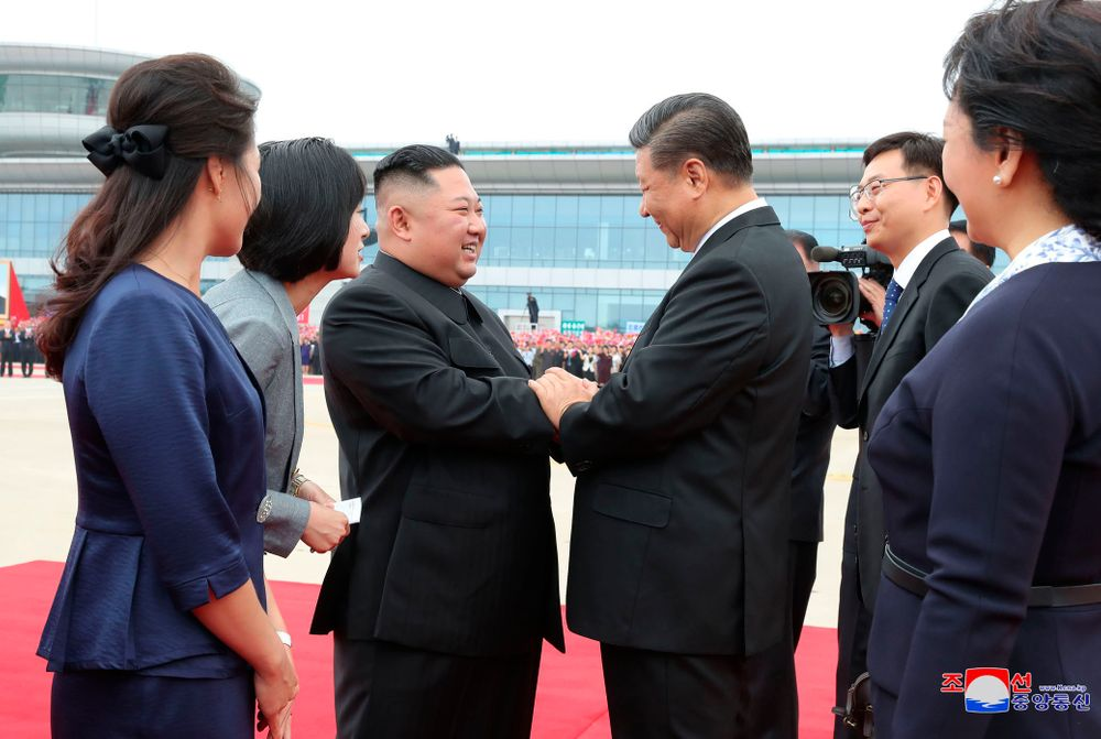 In this Thursday, June 20, 2019, photo provided by the North Korean government, North Korean leader Kim Jong Un, center left, shakes hands with Chinese President Xi Jinping at Pyongyang International Airport in Pyongyang, North Korea. The content of this image is as provided and cannot be independently verified. Korean language watermark on image as provided by source reads:
