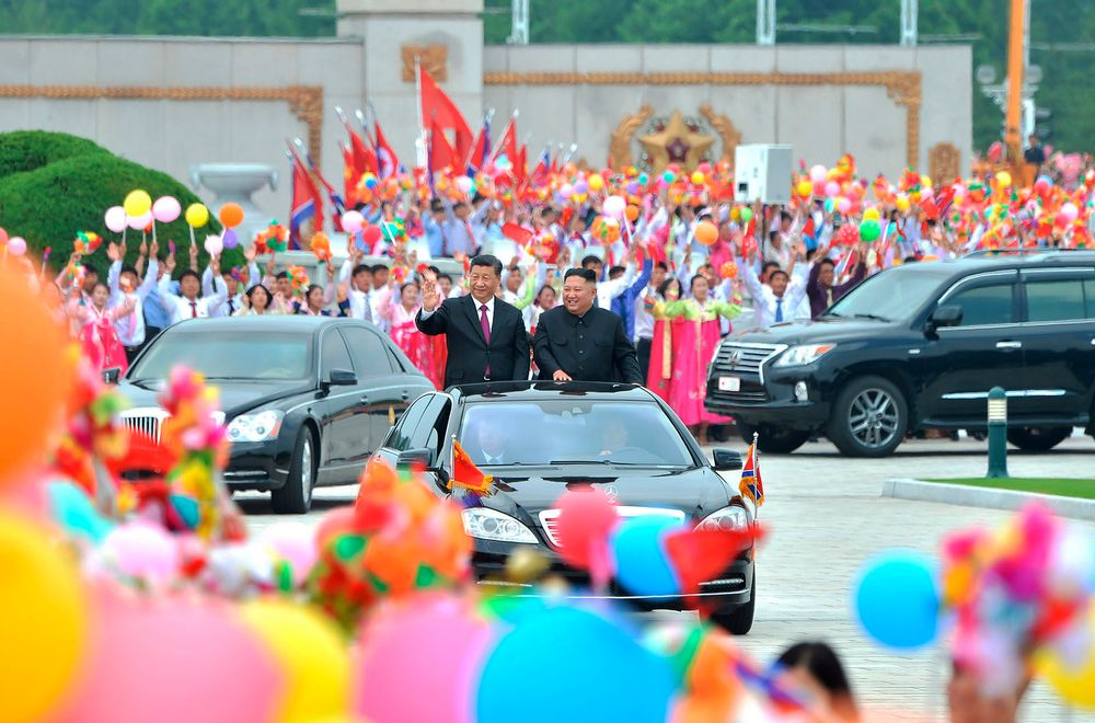 In this Thursday, June 20, 2019, photo provided by the North Korean government, North Korean leader Kim Jong Un, right, and Chinese President Xi Jinping acknowledge welcoming people on a street in Pyongyang, North Korea. The content of this image is as provided and cannot be independently verified.  (Korean Central News Agency/Korea News Service via AP)